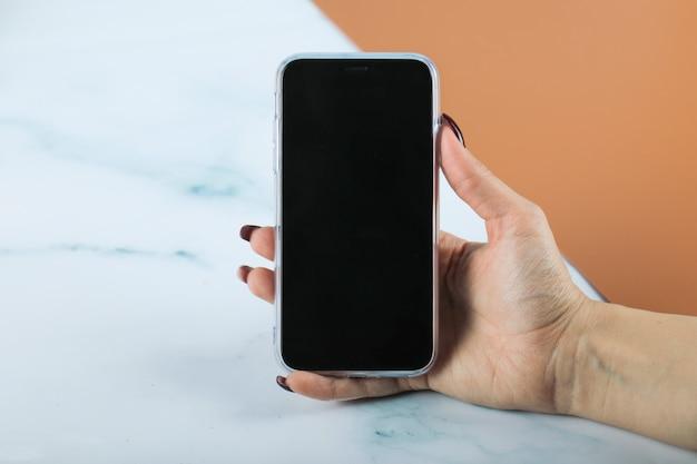 Tomando um smartphone preto na mão