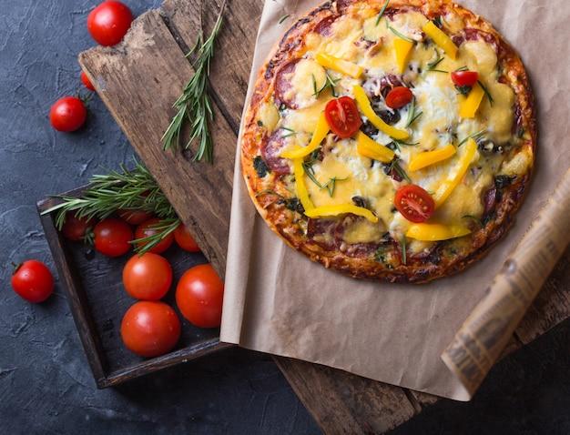 Tomando uma fatia de pizza de calabresa. pizza de pepperoni saboroso no fundo preto, opinião do close up. pizza de mão