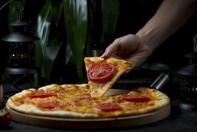 Tomando uma fatia de pizza margarita com fatias de tomate