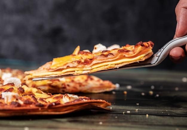 Tomando uma fatia de pizza no preto