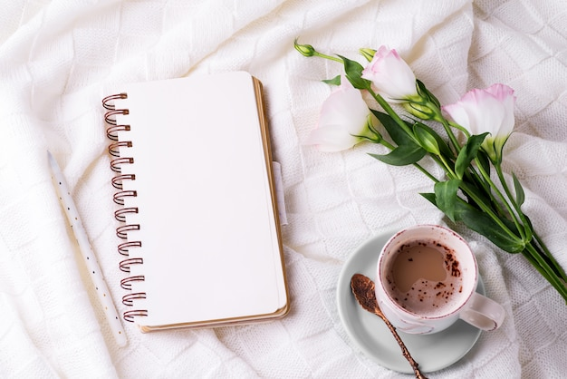 Tomando uma xícara de café, flores eustoma e notebook no cobertor na cama.