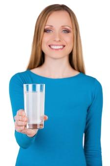 Tomar aspirina! mulher jovem segurando um copo com água e aspirina enquanto fica em pé, isolado no branco