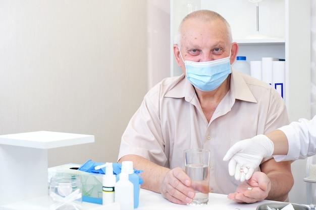 Tomar comprimidos, um copo d'água na mão de uma pessoa idosa. pessoa adulta em um hospital