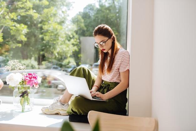Tomar uma decisão. menina morena concentrada usando óculos enquanto trabalha no computador