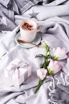 Tomar uma xícara de café com chocolate, flores eustoma e caixa de presente no cobertor na cama.