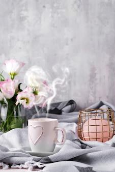 Tomar uma xícara de café com chocolate, flores eustoma e vela no cobertor na cama.
