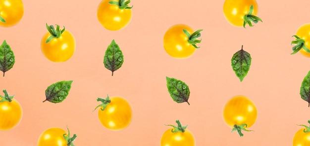 Tomate amarelo e folha de basilo isoladas na vista superior laranja padrão de frutas postura plana