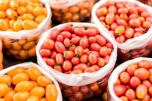 Tomate amarelo e vermelho em saco de plástico Foto Premium