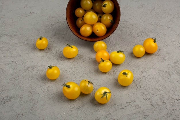 Tomate amarelo maduro fresco dentro e fora do pote redondo marrom no cinza