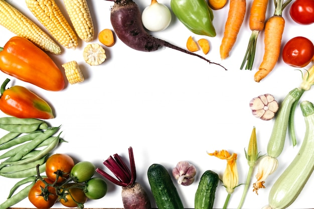 Tomate, cebola, pepino, cenoura, alho, beterraba vermelha, pimenta, abobrinha, milho e haricot verde sobre fundo branco.