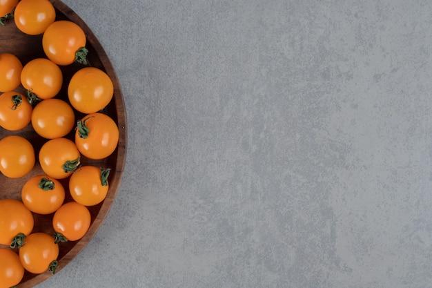 Tomate cereja amarelo isolado na superfície do concreto