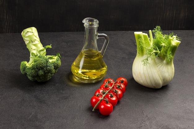 Tomate cereja, brócolis, erva-doce e frasco de vidro com óleo.