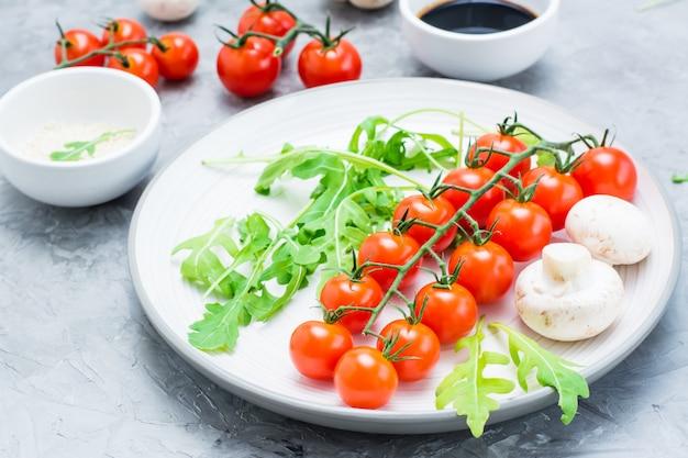 Tomate cereja, cogumelos, rúcula em um prato, gergelim e molho balsâmico em uma tigela