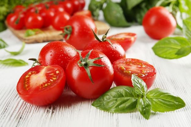 Tomate cereja com manjericão na mesa de madeira close-up