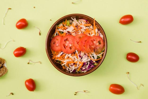 Tomate cereja com tigela de salada ralada e tomates em fundo verde hortelã