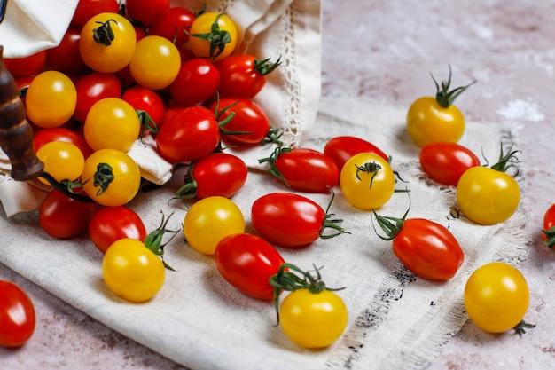 Tomate cereja de várias cores, amarelo e vermelho tomate cereja em uma cesta na luz de fundo