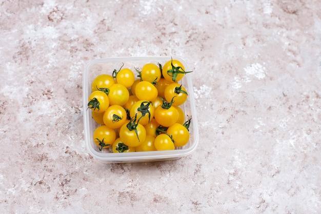 Tomate cereja de várias cores, tomate cereja amarelo e vermelho sobre fundo claro