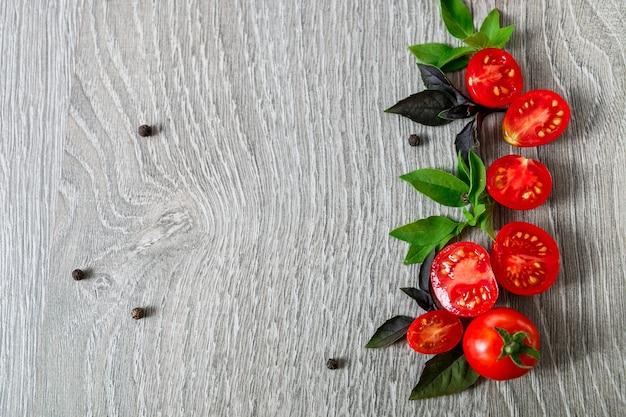 Tomate cereja e manjericão fresco em fundo cinza de madeira. quadro, armação. copie o espaço. postura plana.