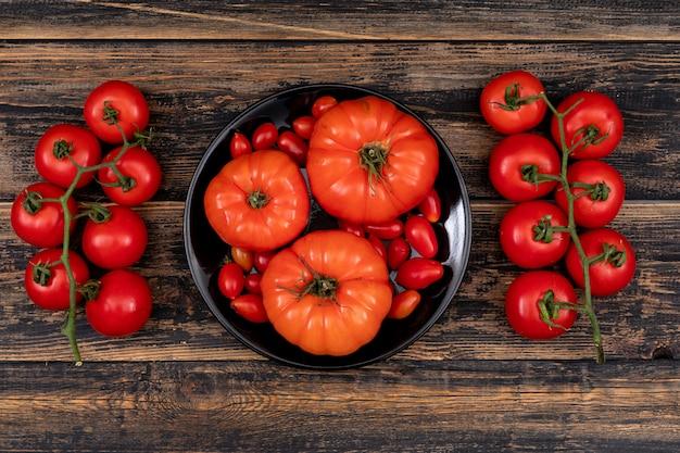 Tomate cereja e tomate grande na tigela de buda em uma mesa de madeira