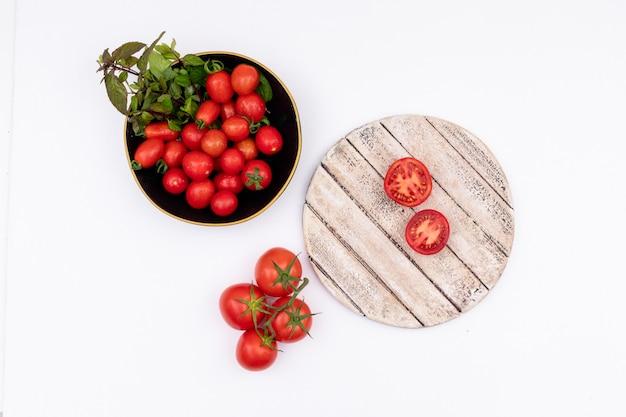 Tomate cereja e verdes em tomates de tigela preta na placa de madeira, isolada na superfície branca