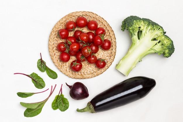 Tomate cereja em prato de vime folhas de brócolis e acelga na mesa