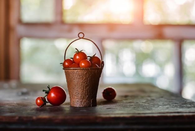 Tomate cereja em um balde velho enferrujado decorativo em um escuro rústico.
