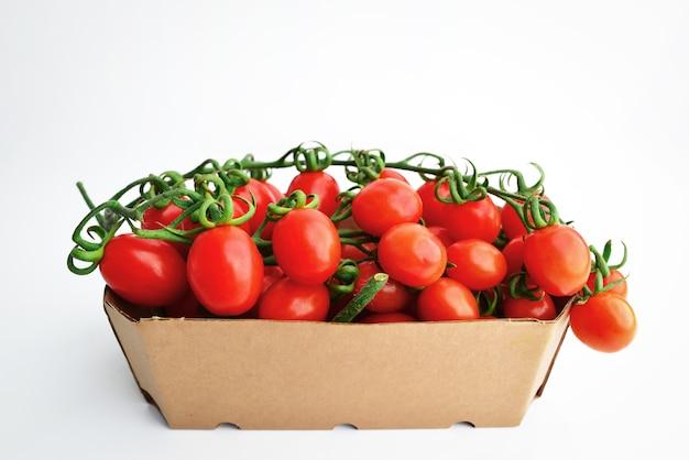 Tomate cereja em um galho em embalagem ecológica. bando de tomates frescos e vermelhos com hastes verdes isoladas no espaço de fundo branco para texto.
