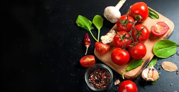 Tomate cereja em um galho, folhas de espinafre e especiarias