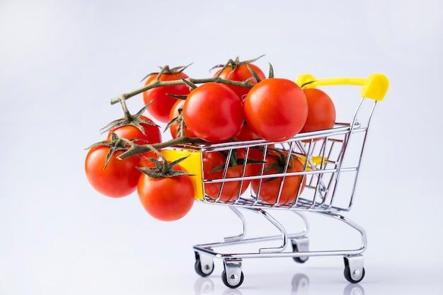 Tomate cereja em um pequeno carrinho isolado no branco