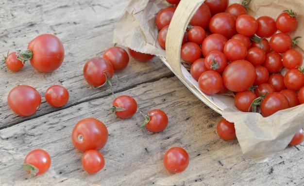 Tomate cereja fresco derramado de uma pequena cesta em um fundo rústico de madeira