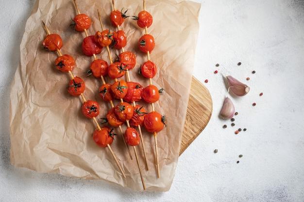 Tomate cereja grelhado no espeto, coloque no papel manteiga. cozido com azeite, alho, sal e pimenta