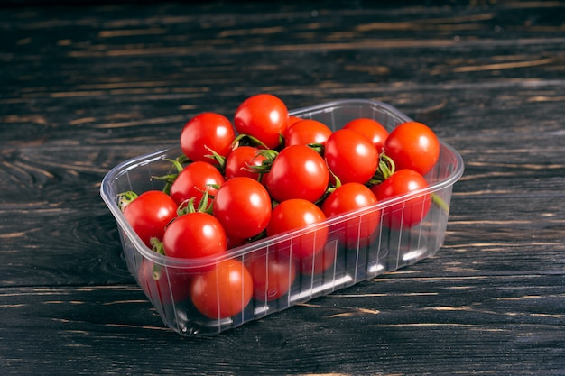 Tomate cereja na caixa de plástico sobre a mesa de madeira
