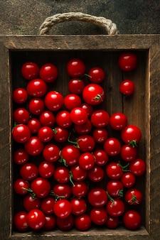 Tomate cereja na velha bandeja de madeira na caixa rústica de madeira, vista superior