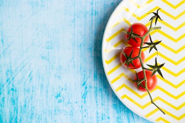 Tomate cereja no prato listrado amarelo