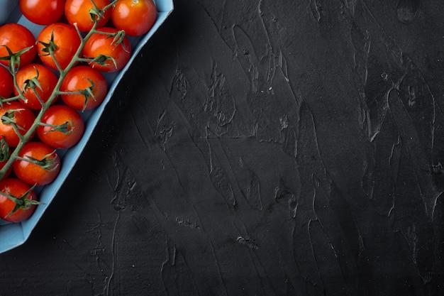Tomate cereja orgânico vermelho fresco, na mesa preta
