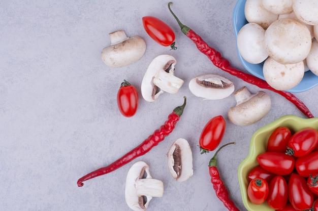 Tomate cereja, pimenta e cogumelos na superfície cinza