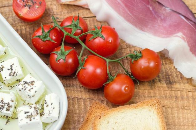 Tomate cereja, queijo e prosciutto com torrada na mesa de madeira
