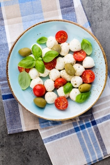 Tomate cereja, queijo mussarela, manjericão e especiarias no quadro-negro de pedra ardósia cinza. ingredientes da salada caprese tradicional italiana. comida mediterrânea.