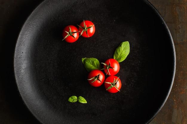 Tomate cereja vermelho em um prato preto