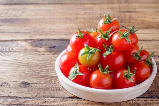 Tomate cereja vermelho em uma tigela de cerâmica na mesa de madeira