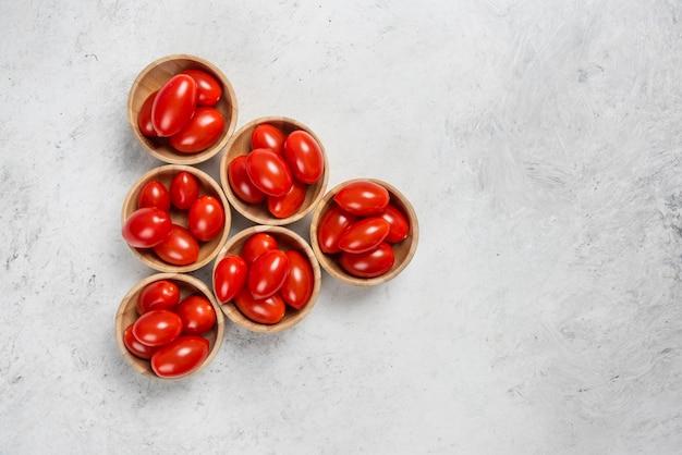 Tomate cereja vermelho fresco em tigelas de madeira.