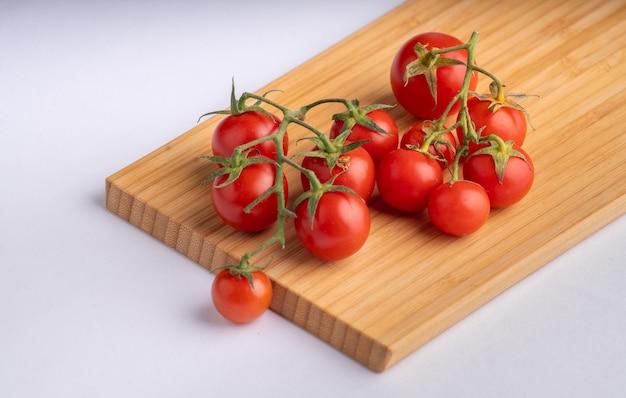 Tomate cereja vermelho na placa de madeira com branco