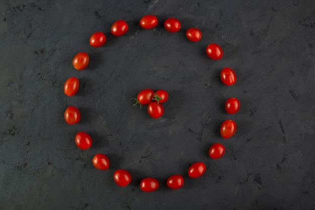 Tomate cereja vitamina madura madura fresca enriquecida em forma redonda pequenos tomates cereja vermelhos na mesa escura