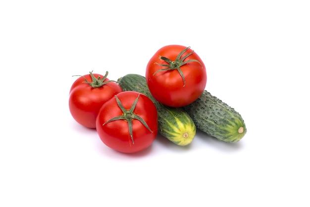 Tomate com pepino em fundo branco com traçado de recorte. legumes maduros isolados no fundo branco.