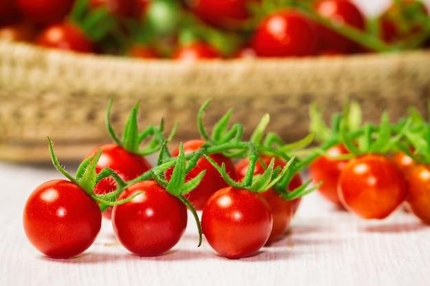 Tomate de cereja fresco na cesta de madeira. vista lateral, foco seletivo no primeiro plano.