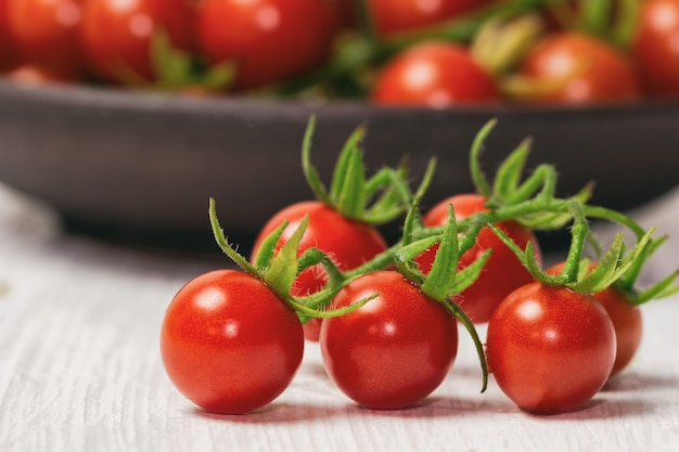 Tomate de cereja fresco na tabela de madeira branca.
