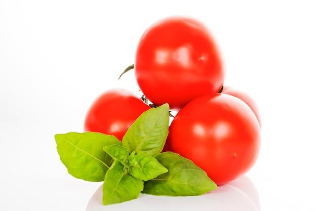 Tomate e manjericão em fundo branco em estúdio