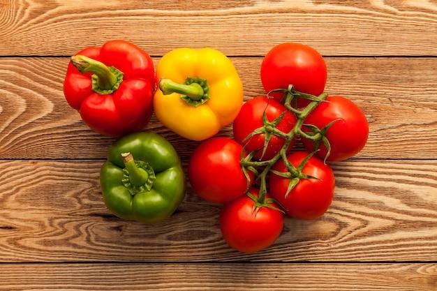 Tomate e pimentão em um fundo de madeira