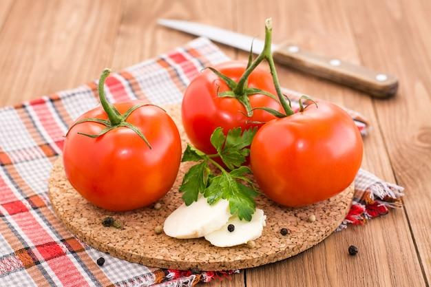 Tomate, fatias de queijo e salsa em um substrato em uma mesa de madeira