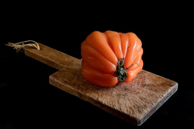 Tomate feio suculento colorido na tábua de madeira sobre uma mesa preta, estilo rústico e chave baixa